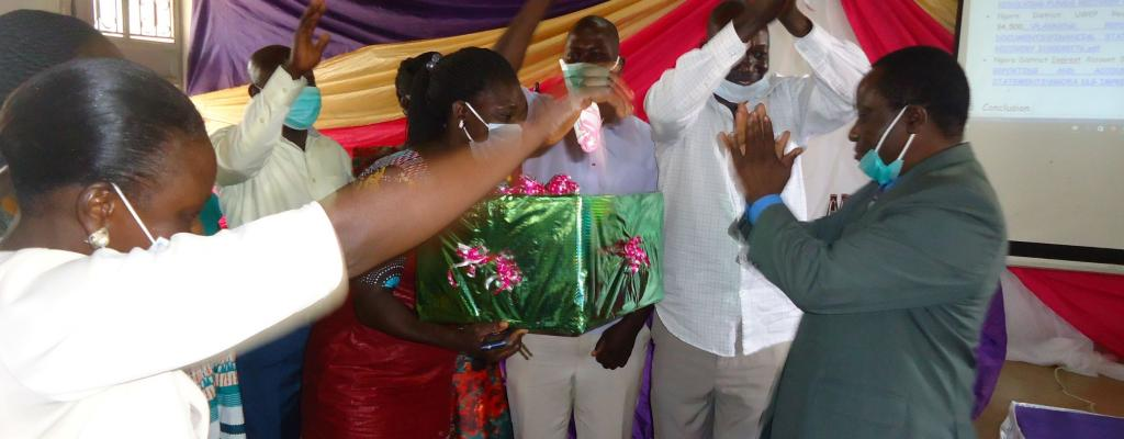 CAO Mawejje Andrew Hands over a gift to support staff